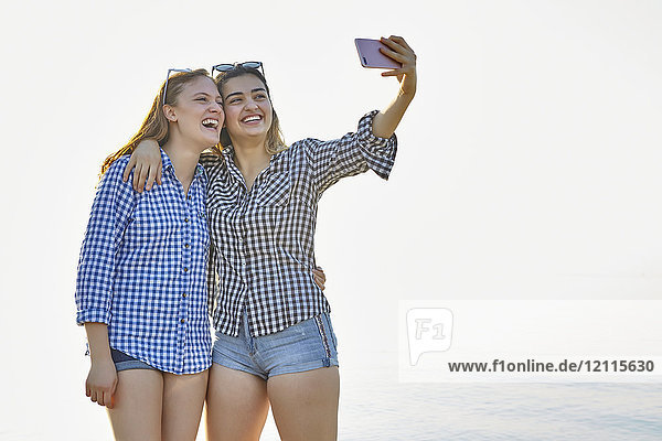 Two teenage girls take a self-portrait as they stand in an embrace at sunset at the lake  Woodbine Beach; Toronto  Ontario  Canada