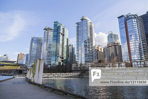 The walking path on the public boat dock in downtown Vancouver along the seawall at the Coal Harbour waterfront neighbourhood with a view of skyrise condo towers and hotels on the skyline; Vancouver  British Columbia  Canada