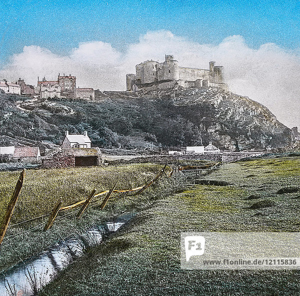 """Magic Lantern slide circa 1900 hand coloured. created in 1887. A tour of North Wales. 39.Harlech Castle,  from the Meadows.— This fine Castle is the remains of a once important fortress,  situated on an elevated rock about half-a-mile from the sea. We are at once struck with the beauty of its situation and strength,  a high perpendicular cliff,  on the side nearest the sea,  rendering it inaccessible. Like most of the other castles in the principality,  this owes its erection to Edward I. Its siege bv Edward IV.,  when held by a Welsh warrior for the House of Lancaster,  gave rise to that fine and popular air,  """" The March of the Men of Harlech. A magnificent view of the Snowdonian range and Car¬narvonshire mountains is obtained from the Castle itself,  Harlech means bold rock. Ten miles further is"""