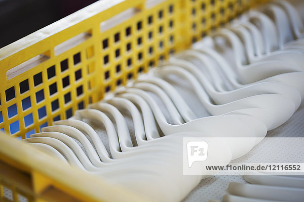 Close up of white porcelain spoons in a yellow plastic tray in a Japanese porcelain workshop.