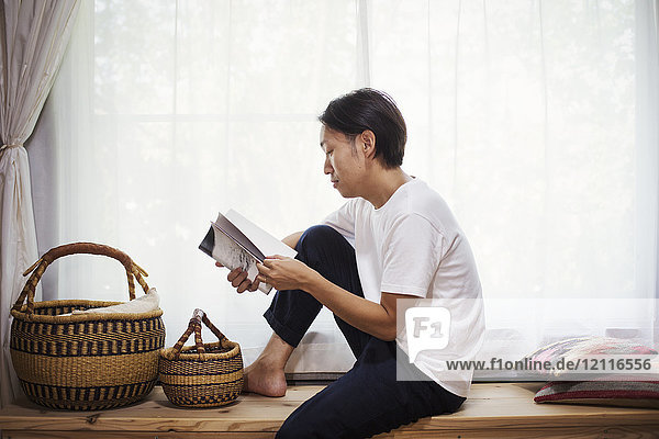 Man sitting indoors on a wooden bench with baskets  crossed legs  reading.