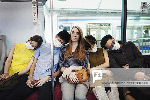 Fünf Personen mit Staubmasken  die nebeneinander in einem U-Bahn-Zug sitzen  Pendler aus Tokio.