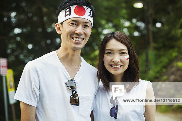 Portrait of man wearing headband and young woman with brown hair  Japanese flag painted on her cheek  smiling at camera.