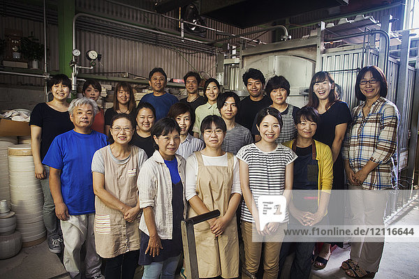 Group portrait of the staff of a Japanese porcelain workshop standing in front of kiln  smiling at camera.