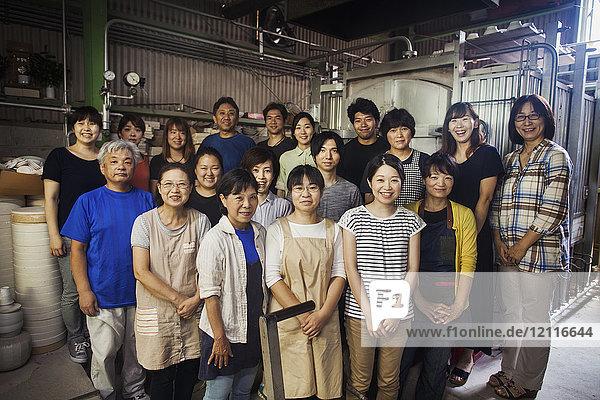 Gruppenporträt der Mitarbeiter einer japanischen Porzellanwerkstatt  die vor dem Ofen stehen und in die Kamera lächeln.