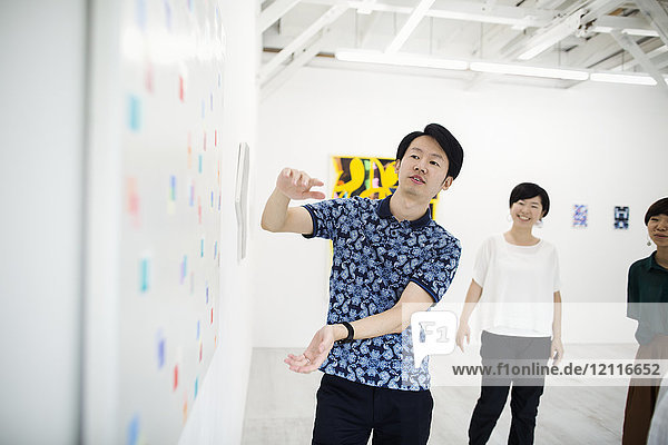 Man wearing blue shirt standing next to modern painting on white wall in art gallery  two women standing in background..