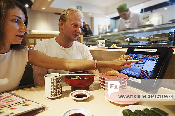 Young man and woman sitting at a table in an Asian Fast Food restaurant  eating sushi  looking at touch screen on their table.