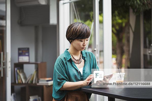 Frau mit schwarzen Haaren in grünem Hemd  die in einem Straßencafé am Tisch sitzt und ein digitales Tablet hält.