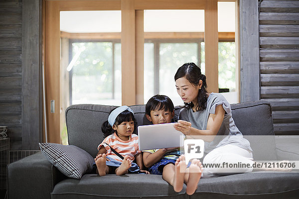 Woman  boy and young girl sitting on a grey sofa  looking at digital tablet.
