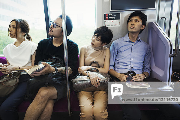 Four people sitting sidy by side on a subway train  Tokyo commuters.