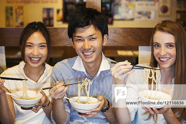 Three smiling people sitting sidy by side at a table in a restaurant  eating from bowls using chopsticks.
