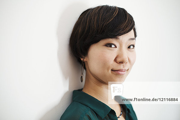Frau mit kurzen schwarzen Haaren und grünem Hemd steht in der Kunstgalerie und lächelt in die Kamera.