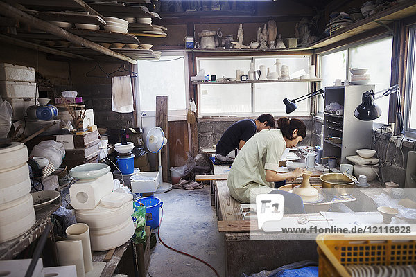 Woman working in a Japanese porcelain workshop  sitting at a potter's wheel  throwing bowl.