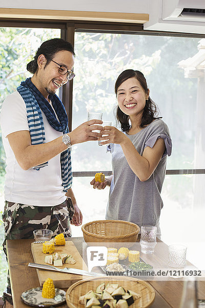 Smiling man and woman standing indoors by a table set with food  holding drinking glasses  toasting.