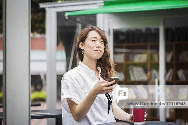 Frau mit braunen Haaren  die ein weißes Hemd trägt  im Freien steht und Handy und Pappbecher hält.
