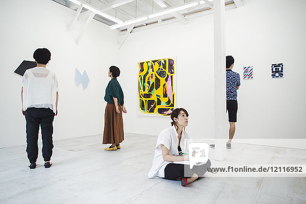Woman with black hair sitting on floor in art gallery with pen and paper  looking at modern painting  three people standing in front of artworks.