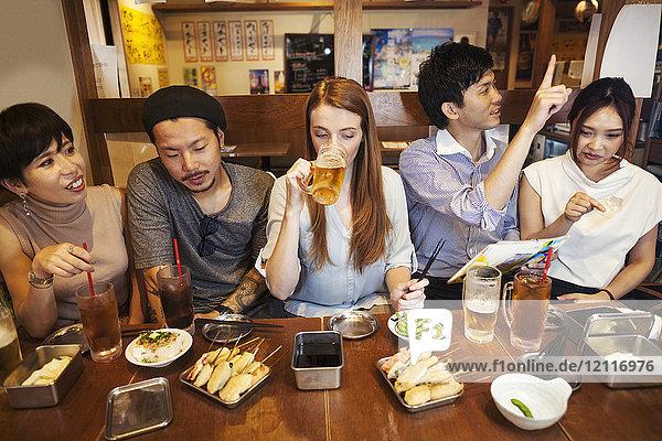 Fünf Personen sitzen nebeneinander an einem Tisch in einem Restaurant  essen und trinken Bier.