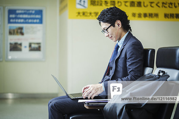 Businessman wearing suit and glasses sitting at train station  working on laptop.
