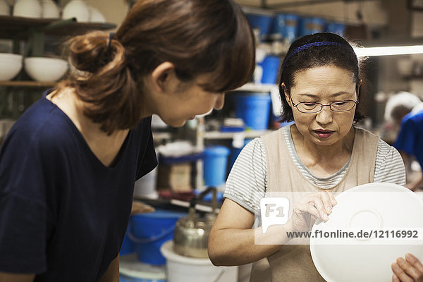 Two women standing in a Japanese porcelain workshop  inspecting a white bowl.