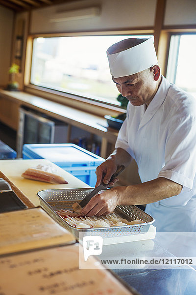 Chef working at a counter at a Japanese sushi restaurant  preparing fish in metal tray.