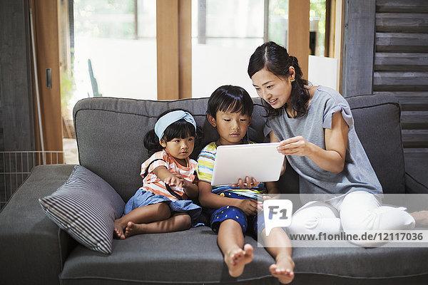 Frau  Junge und junges Mädchen sitzen auf einem grauen Sofa und schauen auf ein digitales Tablett.
