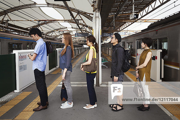 Five people standing in a row on a subway platform  waiting in line  Tokyo commuters.