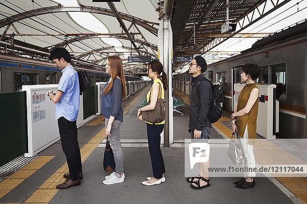 Fünf Menschen stehen in einer Reihe auf einem U-Bahn-Bahnsteig und warten in der Schlange  Tokio-Pendler.