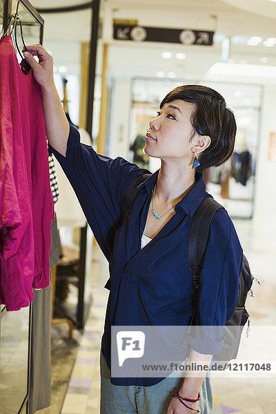 Frau mit schwarzen Haaren und blauem Hemd steht im Haus und betrachtet Kleidung in einem Geschäft.