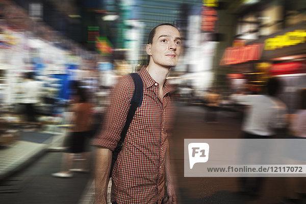 Ein westlicher Mann nachts auf der Straße in Tokio. Ein Tourist in einer städtischen Umgebung  verschwommene Bewegung.