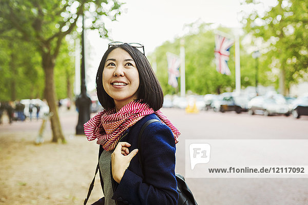Lächelnde Frau mit schwarzen Haaren in blauer Jacke und rotem Schal  die am Rand einer baumgesäumten Stadtstraße steht.