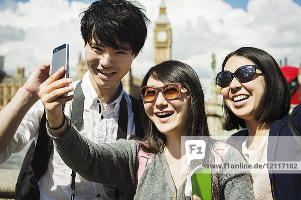 Smiling man and two women with black hair taking selfie with smartphone  standing on Westminster Bridge over the River Thames  London  with the Houses of Parliament and Big Ben in the background.