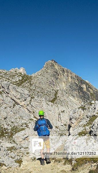Wanderer mit Kletterhelm auf Wanderweg zum Nuvolau  Ausblick auf Gipfel Nuvolau mit Rifugio Nuvolau  Dolomiten  Südtirol  Trentino-Alto Adige  Italien  Europa