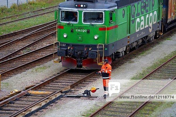 Eisenbahnarbeiter  wartet vor Lokomotive auf den Abflug des Güterzuges am Bahnhof  Ystad  Scania  Schweden  Europa