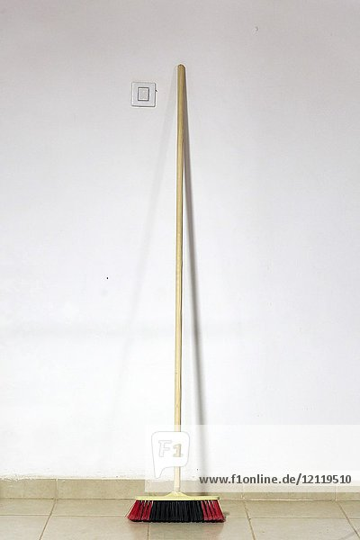 Broom leans against a wall.