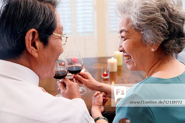 Elderly couples drink red wine