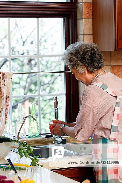 The old woman is washing vegetables in the kitchen