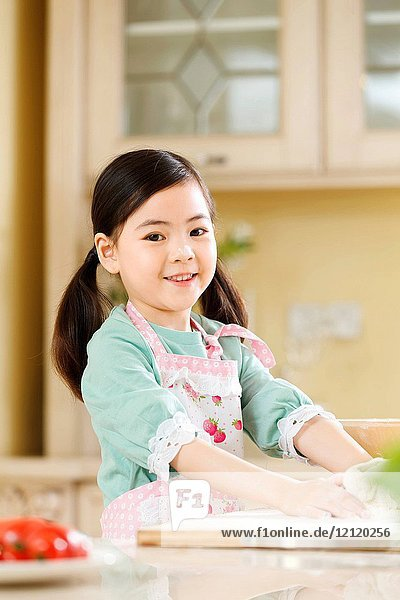 The little girl is in the kitchen