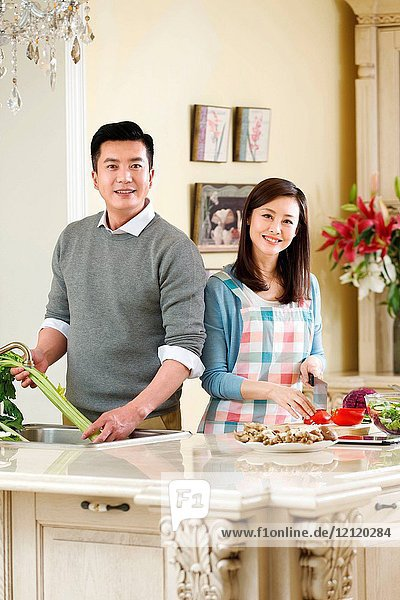 The middle-aged couple are in the kitchen
