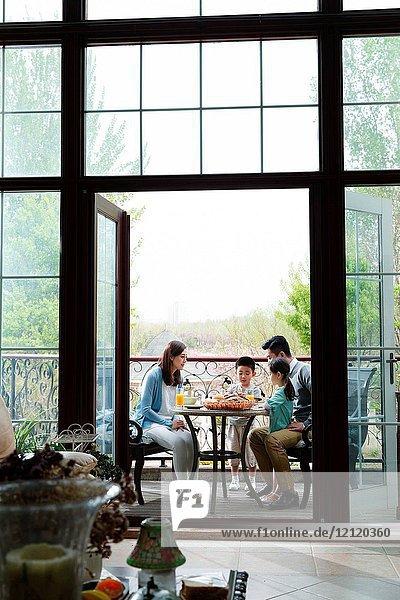 Happy families eat breakfast on the terrace
