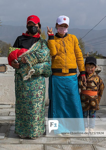 Tibetan pilgrims with traditional and modern clothes in Shachong monastery  Qinghai Province  Wayaotai  China.
