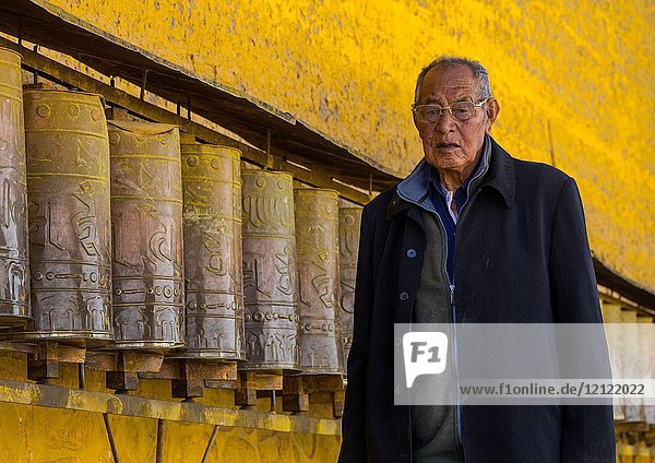 Tibetan pilgrim man turning huge prayer wheels in Rongwo monastery  Tongren County  Longwu  China.