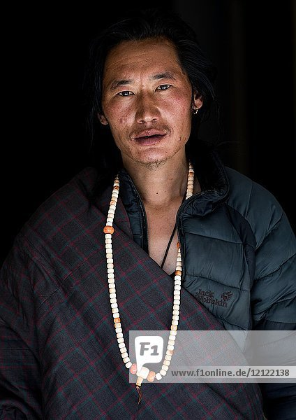 Portrait of a tibetan nomad man with a necklace  Qinghai province  Tsekhog  China.