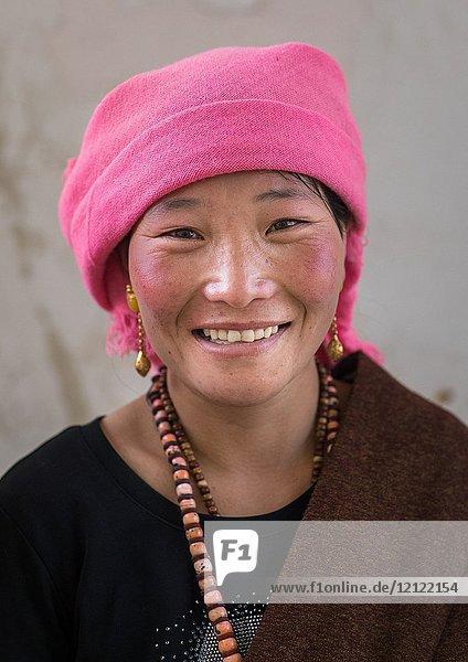 Portrait of a tibetan nomad woman with a pink headwear  Qinghai province  Tsekhog  China.