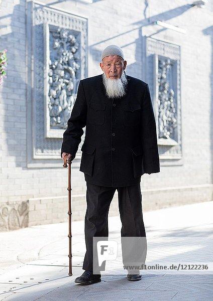Hui muslim man walking with cane in the street  Gansu province  Linxia  China.