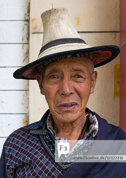 Portrait of an old tibetan man with a traditional and conical hat  Tongren County  Longwu  China.