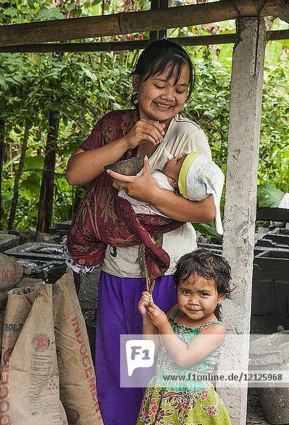 Woman with daughter feeding her baby from a coconut shell in the village of Tegalalang  Gianyar  Bali  Indonesia.