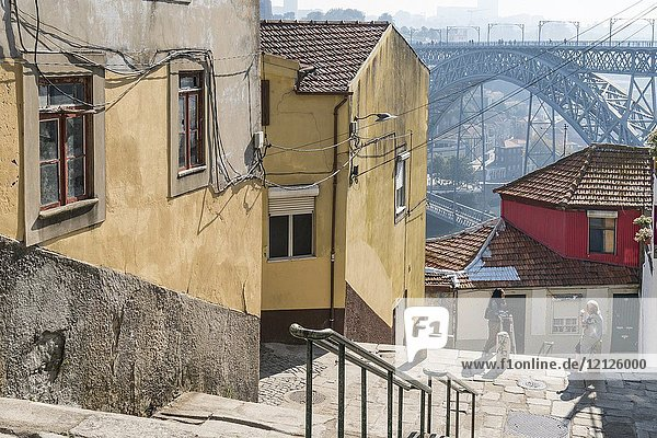 Steps leading down to the River Douro waterfront in the Ribeira district of Porto  Portugal. with the Dom Luis I Bridge in background.