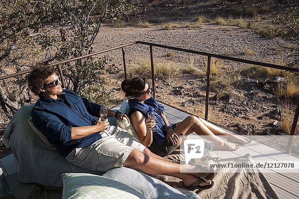 Young couple enjoying a drink at Huab Under Canvas  Damaraland  Namibia  Africa.