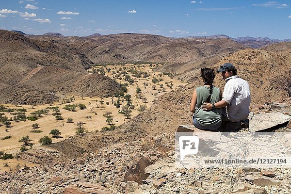Couple overlooking Huab River in Damaraland - Huab Under Canvas  Damaraland  Namibia  Africa.