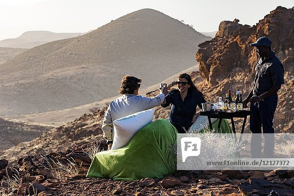 Couple enjoying sundowner while overlooking vast red rock landscape of Damaraland - Huab Under Canvas  Damaraland  Namibia  Africa.